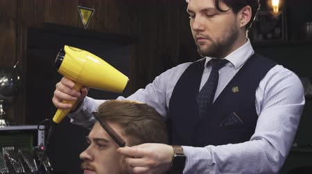 barbering : Sliding shot of a handsome young man smiling while professional barber drying his hair with a blow dryer service consumerism fashion barbering styling barbershop occupation job.