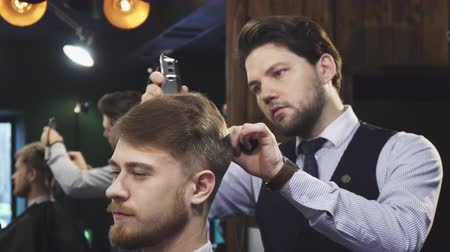 barbering : Attractive professional barber working at his barbershop styling hair of his client young handsome man getting a haircut barbering satisfaction relaxation lifestyle occupation consumerism. Stock Footage