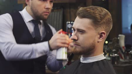 barbering : Close up of a young handsome man smiling while professional barber finishing styling his hair with fire treatment split ends professionalism flames burning service barbering barbershop.