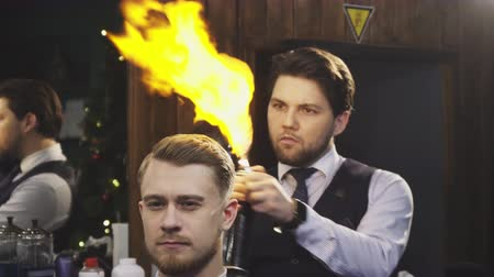 barbering : Professional barber using burning fire treatment finishing haircut and styling for his client service dangerous modern technique occupation job consumerism unusual barbering barbershop.
