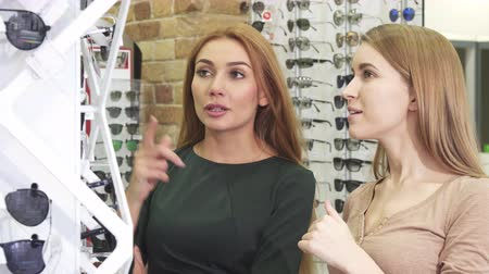 vision care : Beautiful cheerful young women talking choosing sunglasses from the display at the optometrist store eyewear shopping friendship retail sales optics optic glasses communication. Stock Footage