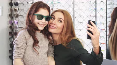 optyk : Gorgeous woman taking selfies with her cute little daughter while shopping for sunglasses at eyewear store optometrist optics family bonding technology social media lifestyle consumerism buying.