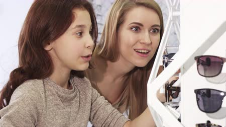 optyk : Close up of a pretty little girl and her older sister shopping for sunglasses choosing eyewear at optometrist consumerism siblings leisure retail sale discount children family bonding sisterhood. Wideo