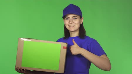 professionalism : Young happy beautiful delivery woman worker smiling to the camera cheerfully holding cardboard box package with copy space showing thumbs up on green background service. Stock Footage