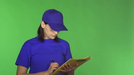 professionalism : Attractive female delivery worker writing on her clipboard smiling to the camera posing on green background copyspace service shipment courier uniform postal occupation concept. Stock Footage