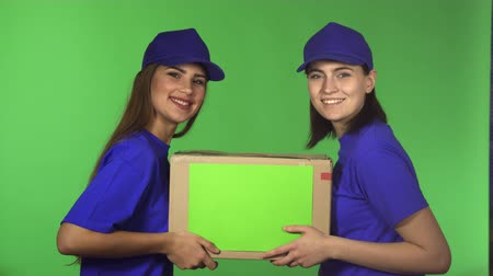 professionalism : Young happy beautiful delivery service female workers smiling joyfully to the camera delivering cardbord box with a copyspace holding the package occupation postal concept.