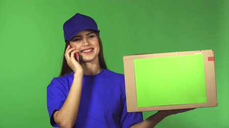 hívó : Young gorgeous delivery woman calling her client on the phone smiling joyfully delivering cardboard box package with a copyspace working with people transportation postal employee.