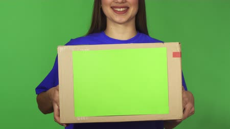 professionalism : Cropped shot of a cheerful professional delivery service worker woman smiling holding cardboard box package with copyspace delivering to the client on green background.