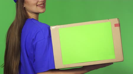 caixa de correio : Cropped rear view shot of a cheerful professional postal worker delivery service female employee smiling joyfully holding cardboard box with copyspace on green background.