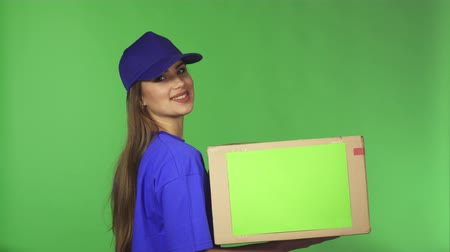 assistência : Young gorgeous professional delivery woman in uniform smiling joyfully showing thumbs up holding cardboard box with copyspace delivering package to the client profession occupation job concept.