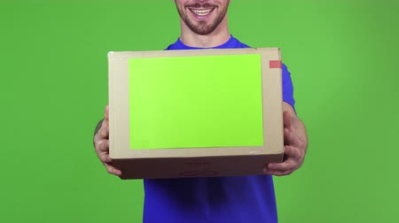 professionalism : Cropped shot of a bearded smiling professional delivery man posing on green background holding out postal package to the client handing cardboard box to the viewer service concept. Stock Footage