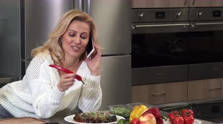 interior : Gorgeous cheerful mature blond haired woman housewife smiling happily talking on the phone at the kitchen preparing to cook dinner culinary cuisine lifestyle leisure healty eating.