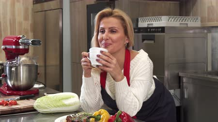 körítés : Happy gorgeous mature housewife smiling joyfully to the camera enjoying drinking coffee at home after cooking at the kitchen femininity maturity lifestyle vitality happiness living.