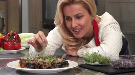 seafood recipe : Close up of a beautiful blonde mature woman cooking for her family at the kitchen smiling joyfully decorating food with greens recipe seafood eating nutrition dinner meal culinary gourmet.