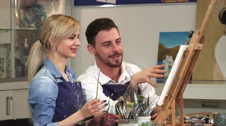 шедевр : Handsome bearded man helping his beautiful girlfriend painting a picture working on a drawing at the Art Studio togetherness couple dating romance love affection artist creativity teamwork concept. Стоковые видеозаписи