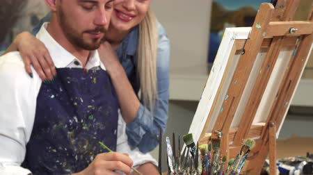 шедевр : Sliding shot of a handsome tattooed bearded young male artist enjoying painting a picture at the Art Studio woth his beautiful happy girlfriend hugging him support happiness love dating romantic. Стоковые видеозаписи