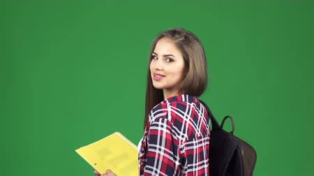 scholarship : Rear view shot of a young beautiful happy female student with books and a backpack smiling joyfully to the camera over her shoulder on green background chromakey education teen concept. Stock Footage