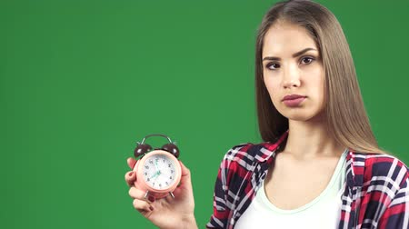 строгий : Studio close up of a beautiful young serious woman looking at the alarm checking time pointing at the clock time management late timing hurry planning lifestyle focused concentrated concept.
