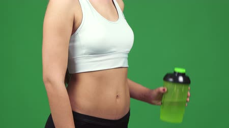 hidratáció : Cropped close up of a sexy fit woman in sports top showing off her stunning body holding bottle of water showing thumbs up nutrition health drinking vitality athletics weight loss fitness.