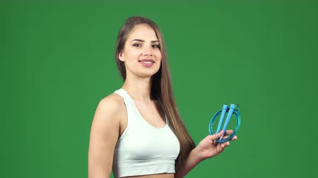 pompki : Happy beautiful young sportswoman smiling showing thumbs up holding jumping rope on green chromakey background crossfit sport motivation cardio exercising gym fitness athletics activity.