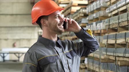 hívó : Cheerful handsome factory worker wearing uniform and hardhat smiling talking on the phone standing at the metalworking manufacturing storage technology communication mability.