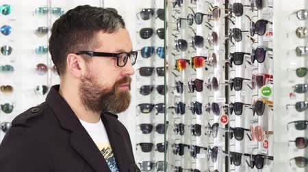 megpróbál : Profile shot of a bearded mature man trying on glasses in front of the mirror shopping for eyewear at the optometrist store consumerism retail customer eyes sight healthy vision.