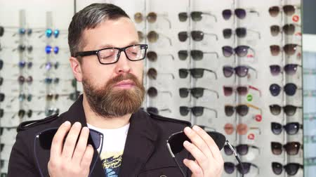 носить : Bearded male customer choosing between two pairs of sunglasses shopping for eyewear at the optometrists store consumerism buying shopping client purchasing fashion style UV protection.