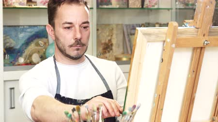 művésziesség : Handsome mature male painter artist painting a picture enjoying working at his studio. Professional artist concentrating examining his artwork occupation designer creativity profession.