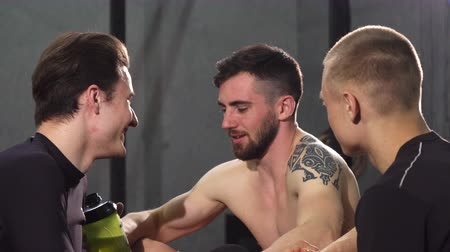 břišní : Handsome bearded shirtless sportsman enjoying talking to his friend at the gym after training laughing cheerfully. Group of male friends resting together after working out. Friendship, communication. Dostupné videozáznamy