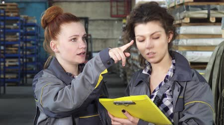 feminism : Beautiful red haired young female factory worker talking to her colleague checking papers together working at the warehouse of a metalworking company. Profession, emancipation concept.