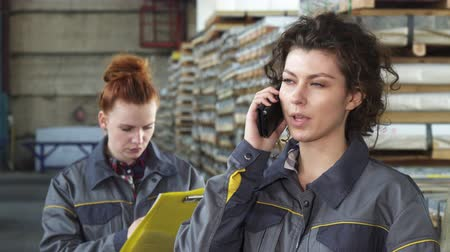 hívó : Close up of a young attractive female technician smiling joyfully talking on the phone at the distribution warehouse her colleague working on the background. Women, technology.