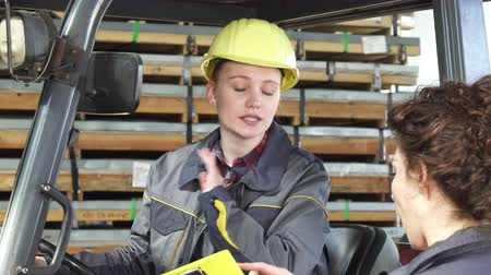 emancipation : Attractive female forklift operator working at the storage wearing protective hardhat talking to her colleague. Professionalism, partnership, distribution, emancipation concept.