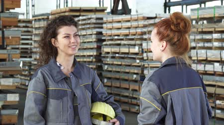hardhat : Young happy female engineer smiling joyfully talking to her colleague high fiving cheerfully celebrating success. Women factory workers. Coworkers communication. Celebration gesturing. Stock Footage