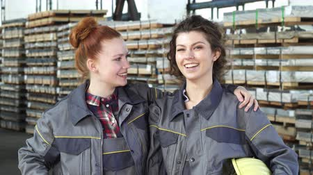 professionalism : Beautiful young women engineers or factory technicians embracing at the metalworking warehouse smiling cheerfully showing thumbs up. Female frienship. Hardware storage concept. Stock Footage