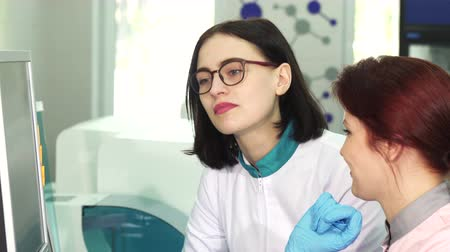 phd : Sliding shot of a young attractive female scientist talking to her assistant using computer together. Two women laboratory workers discussing scientific research. Development, profession. Stock Footage