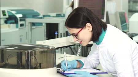 emancipation : Profile shot of an attractive female researcher smiling making notes watching automated analyzer machine at the modern biochemical laboratory. Science, development, technology concept.