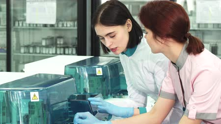 emancipation : Beautiful short haired female biologist and her colleague chemist discussing work while watching automated biochemistry analysing machines at the lab. Communication, teamwork, science.
