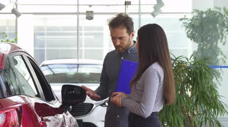 sala de exposição : Professional salesman talking to a young woman at the car dealership salon. Female customer choosing a new automobile at the showroom. Mature auto dealer opening car door for a client.