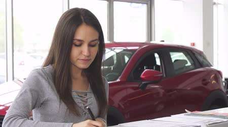 car rental : Attractive woman buying a new car at the dealership and signing papers for insurance. Young female customer filling documents for her new automobile. Consumerism, ownership concept. Stock Footage