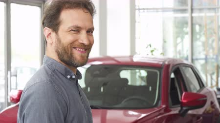 bérlet : Mature bearded handsome man smiling posing in front of his new automobile holding car keys. Happy male customer buying a new auto. Cheerful male driver holding car key. Ownership concept.