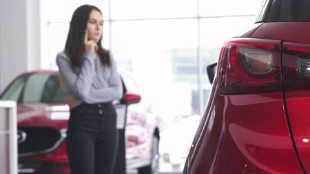 bérlet : Selective focus on car lights on the foreground. Female customer examining cars for sale on the background. Woman shopping for a new vehicle. Buying cars concept. Driving automobile.