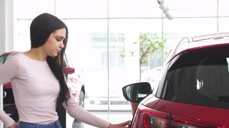 prawo jazdy : Attractive female customer using her smart phone while choosing a new automobile at the dealership salon. Cheerful beautiful woman typing messages on the phone while buying a car.