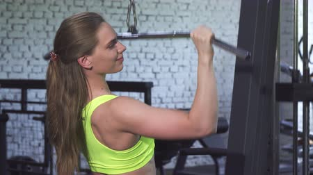 формирование : Beautiful young fitness woman working out at the gym. Attractive sportswoman exercising on lat pull gym machine. Female bodybuilder training. Fitness, sports, motivation concept.