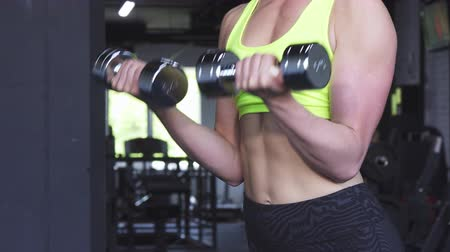 bicep : Cropped shot of a fitness woman with perfect fit and toned sexy body exercising with dumbbells at the gym. Female athlete with abs working out with weights. Body, healthy lifestyle concept.