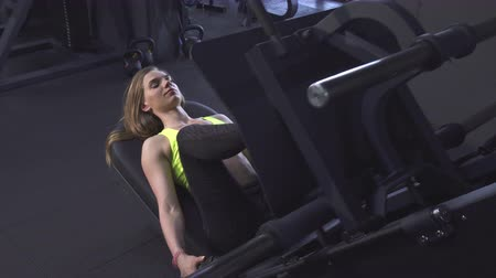 pumping : Beautiful young sportswoman working out at the gym doing leg press exercise. Attractive fit and toned fitness woman training at sports studio using leg press machine. Motivation, bodybuilding.