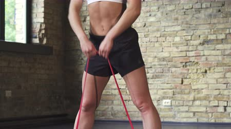 resistência : Sliding low angle shot of a young sportswoman with fit and toned sexy body exercising at the gym using resistance rubber band. Gorgeous fitness woman working out with elastic band.