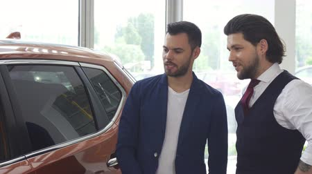 bérlet : Handsome young man discussing a new automobile for sale with his friend while shopping for a car at the dealership showroom. Male friends choosing automobiles.