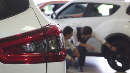 retailer : Selective focus on a car light on the foreground, copy space. Professional car dealer and his male customer examining wheels and tires of an auto on the background. Stock Footage