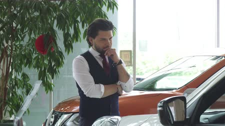 лошадиная сила : Handsome bearded young man looking thoughtfully at the new car at the dealership salon. Attractive businessman choosing an automobile to buy. Transport, consumerism, rental service.
