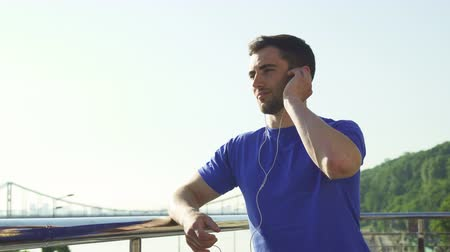 corredor : Low angle shot of a handsome bearded athletic man smiling, looking away, relaxing after morning workout outdoors in the city. Happy male athlete listening to music after exercising.